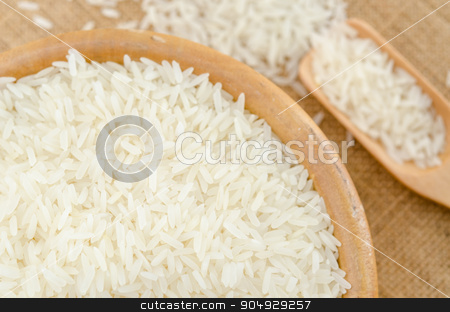 Raw white rice stock photo, Raw white rice in wooden bowl on sack background. by Miss. PENCHAN  PUMILA