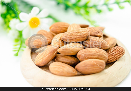 Almond in wooden dish. stock photo, Almond in wooden dish with flower on white background. by Miss. PENCHAN  PUMILA