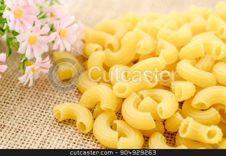 Elbow macaroni noodles with flower. stock photo, Elbow macaroni noodles with flower on sack background. by Miss. PENCHAN  PUMILA