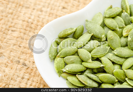 Raw Organic Pumpkin Pepita Seeds in a Bowl. stock photo, Raw Organic Pumpkin Pepita Seeds in a Bowl on sack background. by Miss. PENCHAN  PUMILA