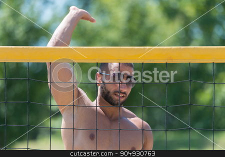 Volleyball Player Pushing Ball Over Net stock photo, Muscular Young Man Playing Beach Volleyball Diving After The Ball by Jasminko Ibrakovic