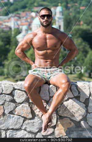 Man Flexing Muscles Outdoors In Summer Time stock photo, Portrait Of A Physically Fit Man Showing His Well Trained Body Outdoors In Summer Time by Jasminko Ibrakovic