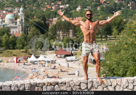 Double Biceps Pose Outdoors In Summer stock photo, Portrait Of A Physically Fit Man Showing His Well Trained Body Outdoors In Summer Time by Jasminko Ibrakovic