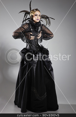 Extravagant lady in a black dress stock photo, Extravagant lady posing in a black dress with a corset, decorated with tulle and black feathers by JRstock