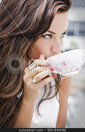 Brunette having a cup of tea stock photo, Fashionable pretty woman drinking tea from an elegant cup by JRstock