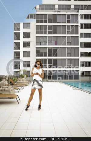 Elegant woman standing in a courtyard stock photo, Elegant woman in a white shirt, striped mini skirt and black heels standing in a courtyard of a condo by JRstock