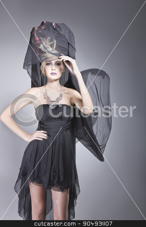 Pretty woman with a long veil stock photo, Pretty woman posing in a short dress and a long black veil, attached to a fashionable hat by JRstock