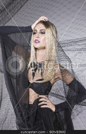 Blonde model with a long veil stock photo, Blonde model with a fashionable makeup posing with a long black veil in a studio by JRstock