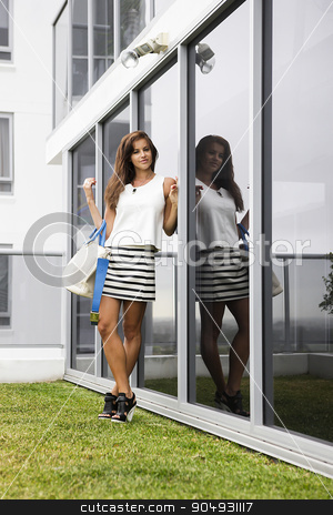 Stylish brunette standing in front of a building stock photo, Stylish brunette in a white blouse and a striped mini skirt standing in front of a glass building by JRstock