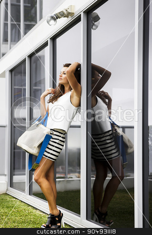 Attractive brunette leaning on a glass window stock photo, Attractive brunette in stkylish clothing leaning on a big glass window by JRstock