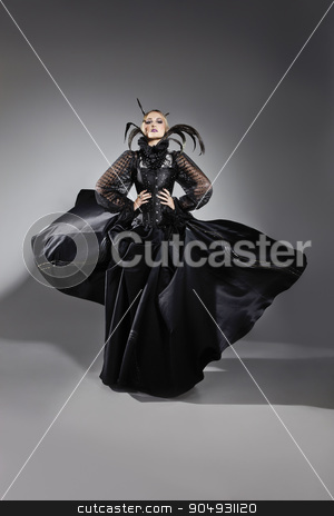 Model showing off extravagant dress  stock photo, Model posing in an extravagant black dress  with tulle and feather decorations in a studio by JRstock