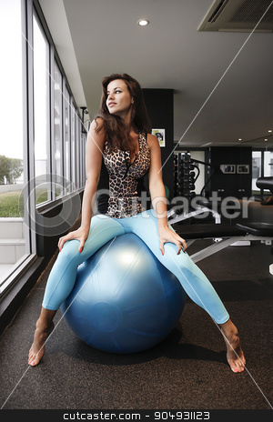 Brunette working out with a blue bouncy ball stock photo, Fit brunette working out with a blue bouncy ball in an empty gym by JRstock