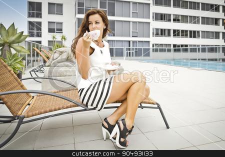 Stylish woman enjoying a cup of tee besides a pool stock photo, Stylish brunette ina mini skirt and high heels enjoying a cup of tee besides a pool by JRstock
