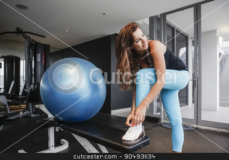 Attractive girl tying her shoelaces in a gym stock photo, Attractive girl in yoga pants  tying her shoelaces in a gym by JRstock