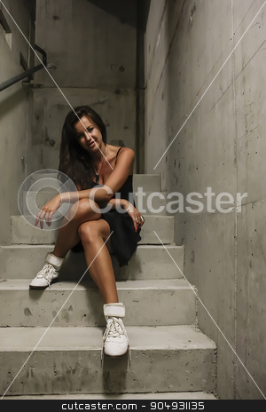 Woman in a black dress sitting on stairs stock photo, Woman in a black dress sitting on grey concrete stairs by JRstock