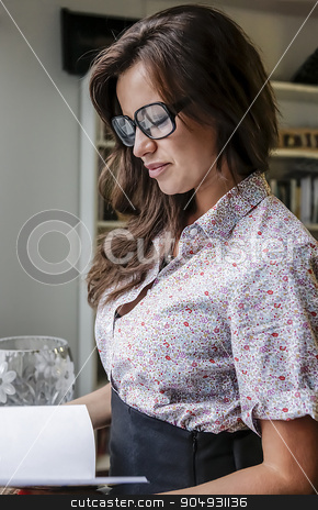 Woman with glasses reading a book stock photo, Beautiful woman with black glasses and a shirt reading a book in a room by JRstock