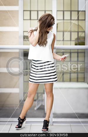 Pretty girl with fashionable clothing using her phone stock photo, Pretty girl with fashionable blouse, striped skirt and black heels using her phone by JRstock