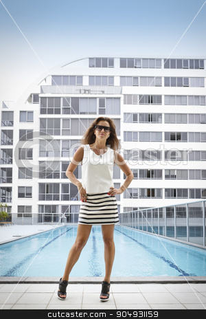 Confident woman posing in front of a pool stock photo, Confident woman in fashionable clothing posing in front of a pool in a courtyard of a condominium by JRstock