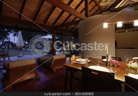 Dining room in late evening stock photo, Modern dining room with a set table and a view to the yard photographed at night by JRstock