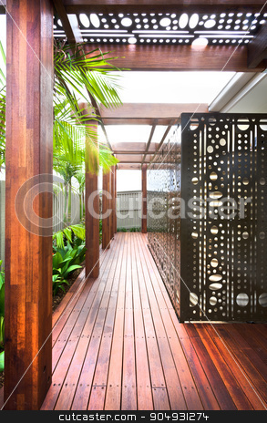 A beautiful eye catching view of house lawn with wooden floor an stock photo, A beautiful eye catching view of house lawn with wooden floor and pillars and plants around it by JRstock