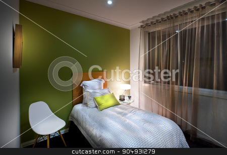 beautiful image of a  carpeted bedroom stock photo, single bed placed in the carpeted room near white chair,background one wall is green and other are the same colour like roof, window is covered with curtain by JRstock