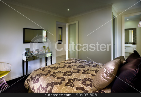 A beautiful bedroom with a bathroom attached and a mrror and tab stock photo, A beautiful bedroom with a bathroom attached and a mrror and table on front of bed with cushion placed on the bed by JRstock
