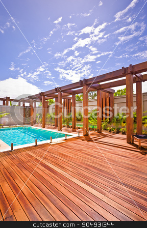 A beautiful view of pool in house in  a sunny day with wooden fl stock photo, A beautiful view of pool in house in  a sunny day with stylish wooden floor and pillars by JRstock
