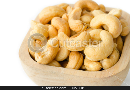 Roasted cashews nuts. stock photo, Roasted cashews nuts in wooden bowl on white background. by Miss. PENCHAN  PUMILA