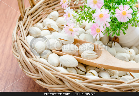Pistachio nuts in wood basket. stock photo, Pistachio nuts in wood basket and woo spoon with flower on wood background. by Miss. PENCHAN  PUMILA