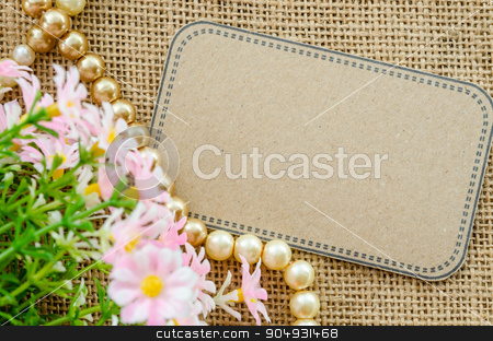Blank brown tag paper. stock photo, Blank brown tag paper with flower on sack background for your text. by Miss. PENCHAN  PUMILA