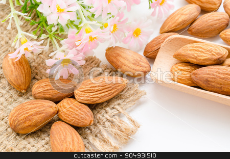 Almonds. stock photo, Almonds in wooden spoon with flower on white background. by Miss. PENCHAN  PUMILA