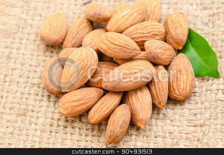 Raw almond with green leaf. stock photo, Raw almond with green leaf on sack background. by Miss. PENCHAN  PUMILA