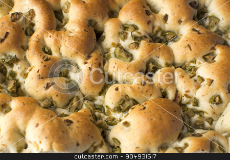 Focaccia - Loaf  stock photo, The focaccia is a traditional loaf - bread from the Italian cuisine and this is closely related to the pizza. in this picture you can see the texture and the spices that made this delicious food. also you can see pieces of green olives and black. by Raul Davila