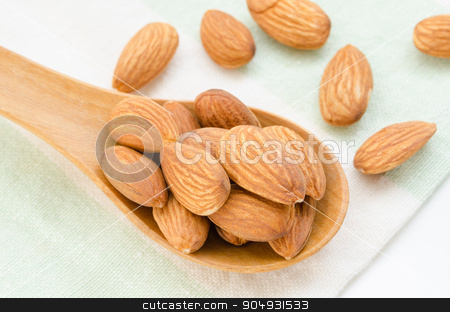 Almond. stock photo, Raw Almond in wood spoon on tablecloth. by Miss. PENCHAN  PUMILA