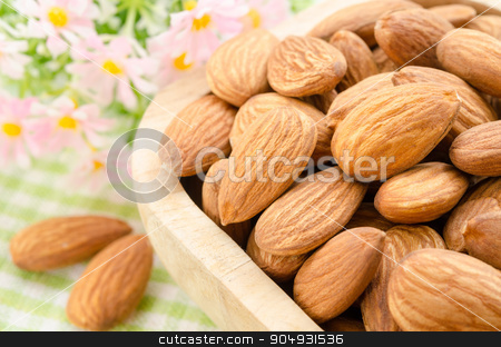 Almond in wooden cup. stock photo, Almond in wooden cup with flower on fabric background. by Miss. PENCHAN  PUMILA