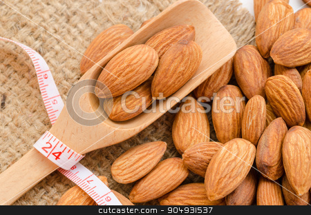 Almond diet concept. stock photo, Almond in wooden spoon with measurement on sackground. Food for Diet concept. by Miss. PENCHAN  PUMILA