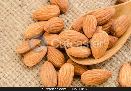 Almonds. stock photo, Almonds in wooden spoon on sack background. by Miss. PENCHAN  PUMILA