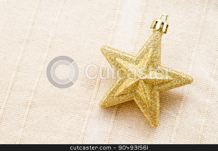 Gold five pointed star christmas decoration. stock photo, Gold five pointed star christmas decoration on fabric background. by Miss. PENCHAN  PUMILA