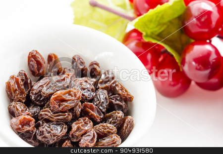 Raisins in bowl with red grapes. stock photo, Raisins in bowl with red grapes on white background close up by Miss. PENCHAN  PUMILA