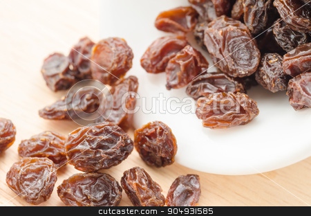 Raisins. stock photo, Raisins in white bowl on wooden background. by Miss. PENCHAN  PUMILA