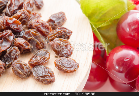 Raisins stock photo, Raisins in wood with red grapes on table close up by Miss. PENCHAN  PUMILA