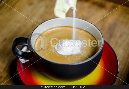 Creamer in to a cup of coffee. stock photo, Hand pouring creamer in to a cup of coffee on wooden background. by Miss. PENCHAN  PUMILA