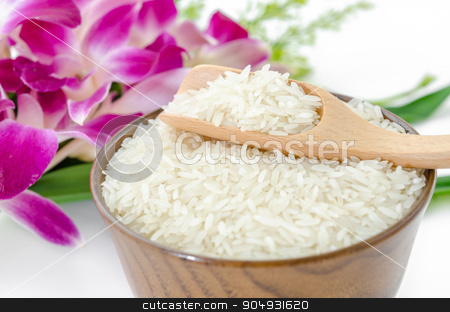 Raw rice jasmine. stock photo, Raw rice jasmine and wooden spoon in wooden bowl with violet orchid flower on white background. by Miss. PENCHAN  PUMILA