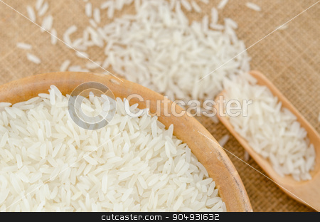 Raw rice in wooden bowl. stock photo, Raw rice in wooden bowl on sack background. by Miss. PENCHAN  PUMILA