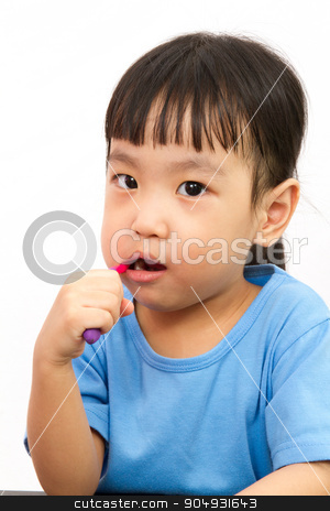 Chinese little girl brushing teeth stock photo, Chinese little girl brushing teeth in plain white isolated background. by Tan Kian Khoon