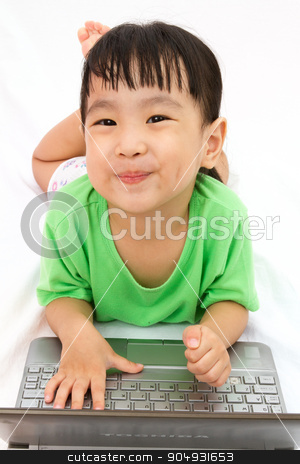 Chinese little girl lying down with laptop stock photo, Chinese little girl lying down with laptop in plain white isolated background. by Tan Kian Khoon