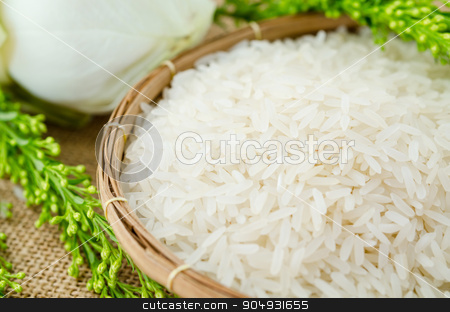 Jasmine rice in weave wooden basket stock photo, Jasmine rice in weave wooden basket on white lotus flower on sack background. by Miss. PENCHAN  PUMILA