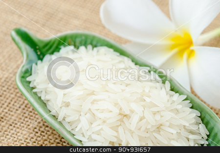 Raw white rice. stock photo, Raw white rice in green cup with flower on sack background. by Miss. PENCHAN  PUMILA