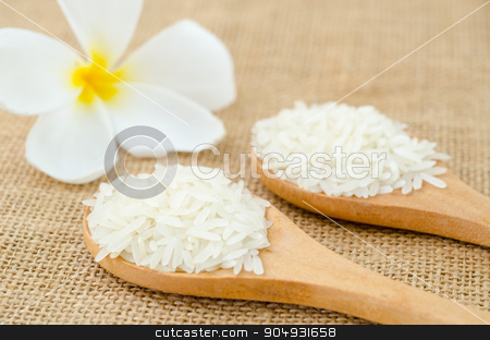 white rice grains in wooden spoon with white flower. stock photo, white rice grains in wooden spoon with white flower on sack background. by Miss. PENCHAN  PUMILA