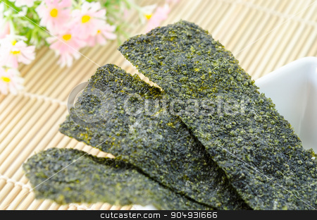 Fried seaweed. stock photo, Fried seaweed in white bowl and wooden fork spoon with flower on bamboo mat. by Miss. PENCHAN  PUMILA